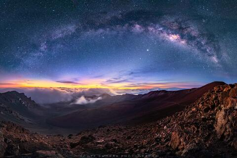 The arc of the Milky Way galaxy and millions of other stars rise above the Haleakala volcanic crater in Maui, Hawaii.