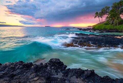 Aquamarine colored waves crash into volcanic Hawaiian rocks at sunset near Wailea-Makena, Maui, Hawaii.