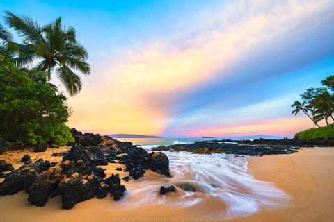 Pastel colors fill the sunrise sky above a secluded beach in Maui, Hawaii.