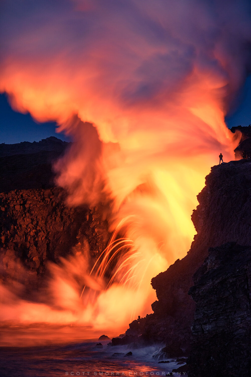 Fine Art Limited Edition of 100 - A lone figure on the edge of the cliffs observes lava pouring directly into the ocean at the...
