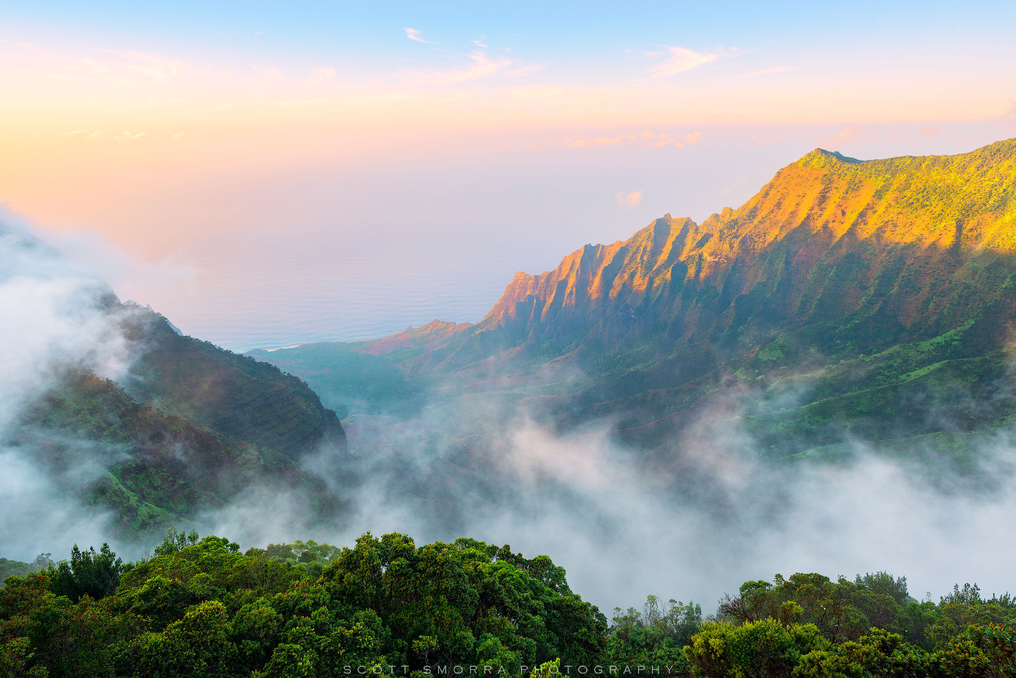 Clouds and fog slowly move in and out of Kalalau Valley on the Hawaiian Island of Kaua'i as sunset light illuminates the pali (cliffs) surrounding the valley.