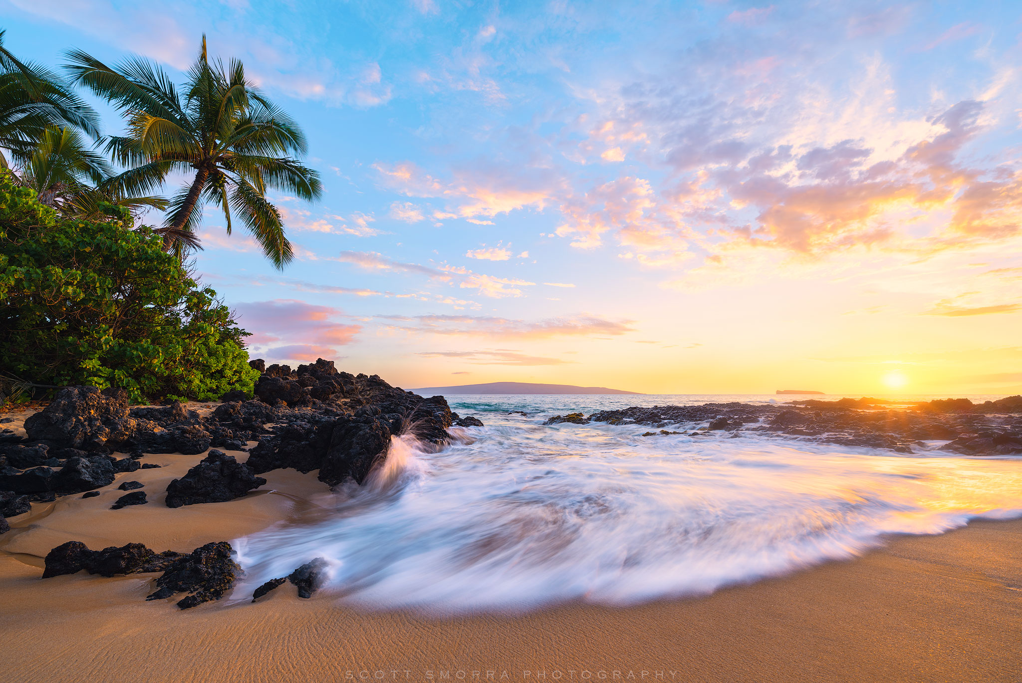 Gentle sunset light illuminates coconut palm trees and rocks at a secluded beach in Maui, Hawaii.
