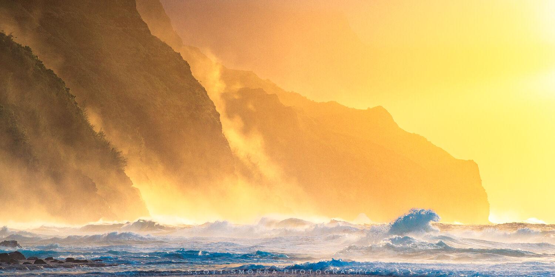 Waves crash into the rocks on the Napali Coast of Kaua'i at sunset.